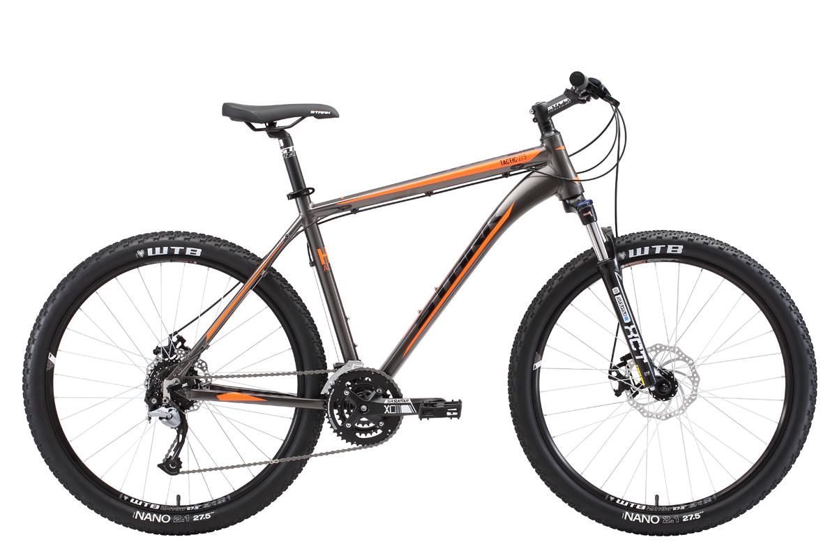 Велосипед Stark Tactic 27.5 D (2018) тёмно-серый/оранжевый/чёрный 18КОЛЕСА 27.5 (НОВЫЙ СТАНДАРТ)<br>Stark Tactic 27.5 D #40;2018#41; - современный горный велосипед с диаметром колёс 27,5 дюймов. Велосипед собран на лёгкой алюминиевой раме, которая изготовлена с применением технологии двойного баттинга. Помимо этого рама имеет полированные швы, внутреннюю проводку тросов и конический рулевой стакан, который обеспечивает дополнительную выносливость. Навесное оборудование - Shimano Acera. Передняя мягкая вилка Suntour имеет ход 80мм и оборудована механическим локаутом - блокировка амортизатора. Stark Tactic 27.5 D оснащён эффективными дисковыми механическими тормозами, с диаметром ротора 180 мм. Трансмиссия велосипеда имеет 27 скоростей, что позволяет велосипедисту поддерживать активный темп и уверенно чувствовать себя на трассах со сложным рельефом местности. Stark Tactic 27.5 D #40;2018#41; - предназначен для любительского кросс-кантри и велотуризма.<br><br>бренд: STARK<br>год: 2018<br>рама: Алюминий (Alloy)<br>вилка: Амортизационная (масло)<br>блокировка амортизатора: Да<br>диаметр колес: 27,5 (650B)<br>тормоза: Дисковые механические<br>уровень оборудования: Продвинутый<br>количество скоростей: 27<br>Цвет: тёмно-серый/оранжевый/чёрный<br>Размер: 18